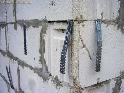 Для крепления фасадных конструкций в кладку заранее закладывают крепежные элементы.