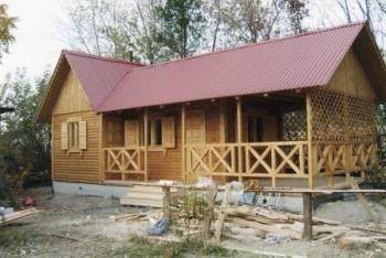 Фото деревянной бани с кухней и террасой.