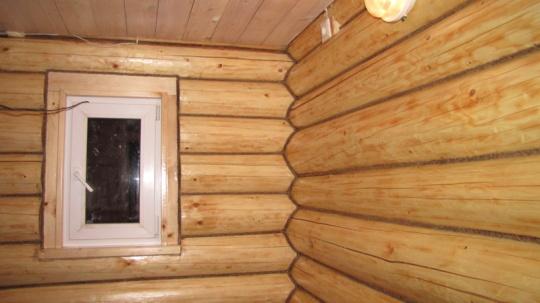 Любительское фото стен из оцилиндрованного бревна, которые дополнительно утеплили путем забивки стыков и покрыли лаком