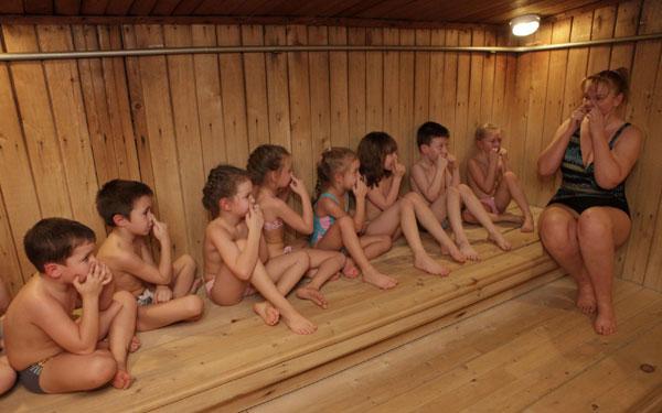 На фото изображен воспитатель детского сада, который знакомит малышей с баней в игровой форме.