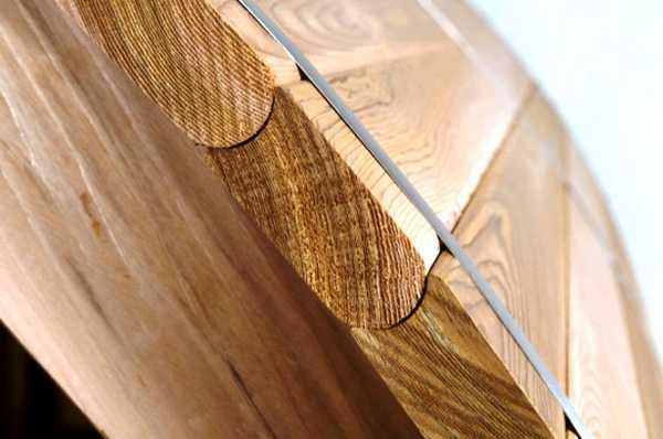 На фото изображены доски, соединенные при помощи закругленной системы «шип-паз» и дополнительно закрепленные стальным декоративным ободом.