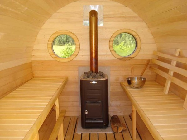 На фото изображены дровяная печь с дымоходом, которая заизолирована от пола и стен специальным материалом, а также полка и скамейка.