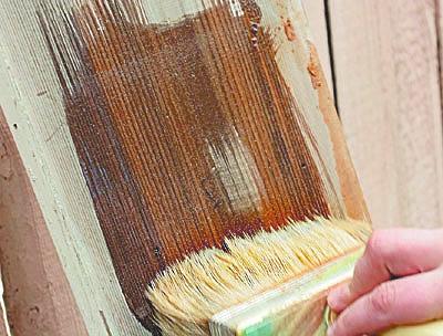 Нанесение красящего вещества на деревянную поверхность.