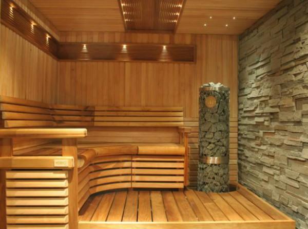 Стена и печка в парилке отделаны рваным камнем (он отлично сочетается с деревом), остальные элементы выполнены из дерева, а на потолке расположено точечное освещение – все это вместе создает уютную и необычную атмосферу.