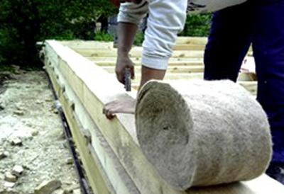 Укладка войлочного межвенцового утеплителя при строительстве сруба