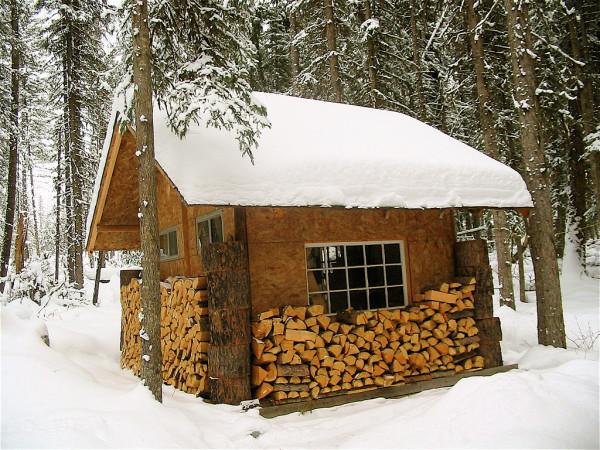 Баня с дровником, оборудованным под удлинёнными скатами её крыши