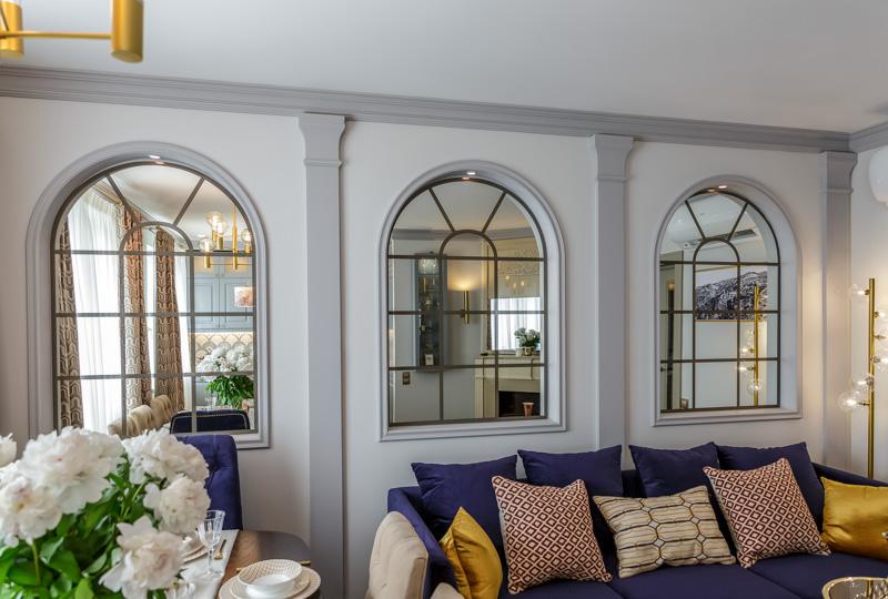 Зеркала, имитирующие окна в интерьере гостиной.