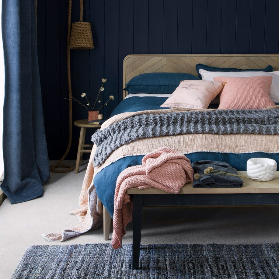Полуночно-синяя спальня с деревянной кроватью и шерстяным ковриком