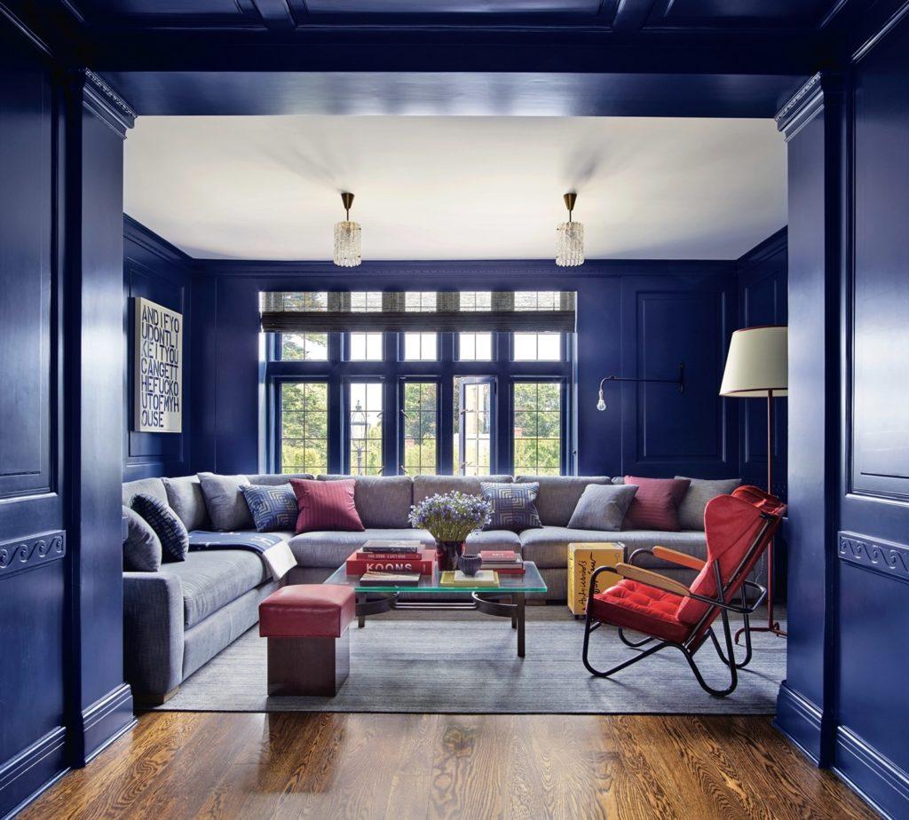 Стены гостиной выкрашены глубоким синим цветом, перекликаются с белым потолком и предметами декора разных цветов