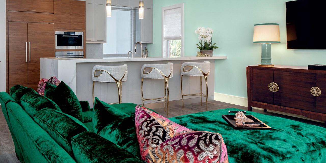 Шикарная зеленая панбархатная софа и нежные светло-зеленые панели помещения