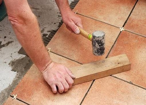Киянкой по плитке, осторожно и легко наносятся удары
