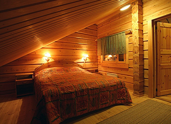 На фото - уютная спальня в мансарде бани.