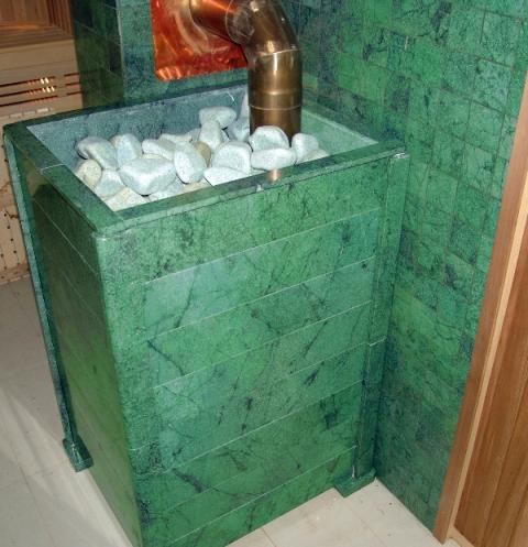 На фото – отделка открытой каменки и стены плиткой из серпентинита