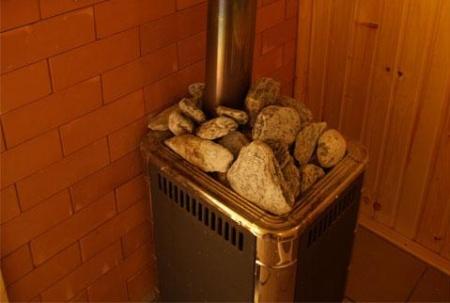 На фото самодельная печь для бани из металла, которая отлично вписывается в интерьер и эффективно работает.