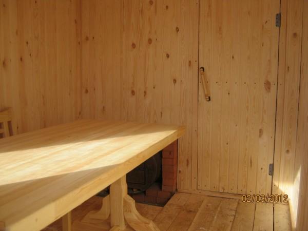 Обшивка стен древесиной и правильное расположение печи для максимальной экономии пространства